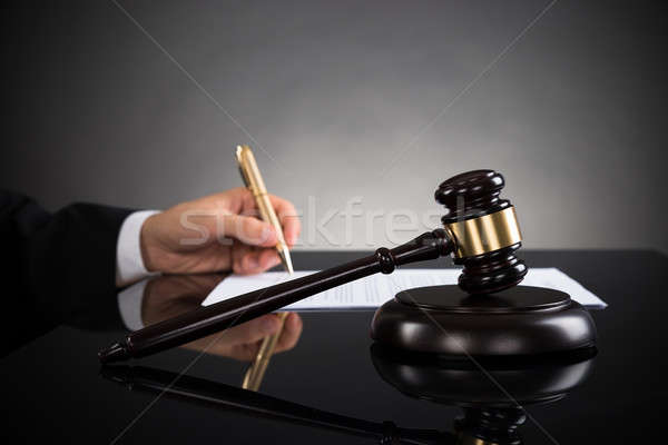 Close-up Of Judge Writing On Paper And Gavel At Desk Stock photo © AndreyPopov