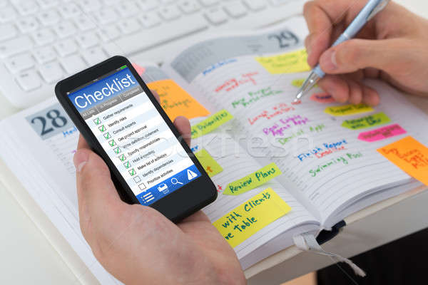 Person Checking List From Mobile Phone And Diary Stock photo © AndreyPopov