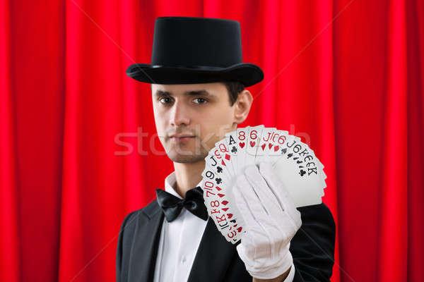 Bűvész tart ki kártyák piros függöny Stock fotó © AndreyPopov