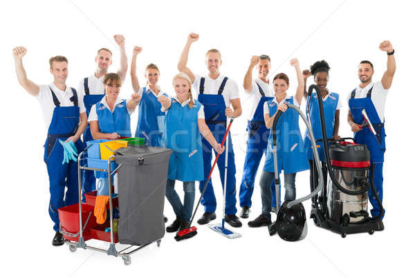 Happy Janitors With Arms Raised Holding Cleaning Equipment Stock photo © AndreyPopov