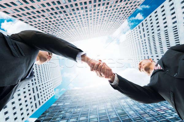 Közvetlenül alatt lövés üzletemberek kézfogás irodaépületek Stock fotó © AndreyPopov