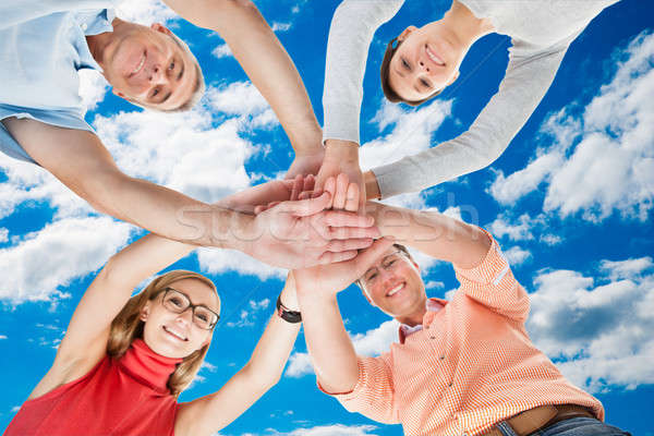 Happy Friends Stacking Hands Against Sky Stock photo © AndreyPopov