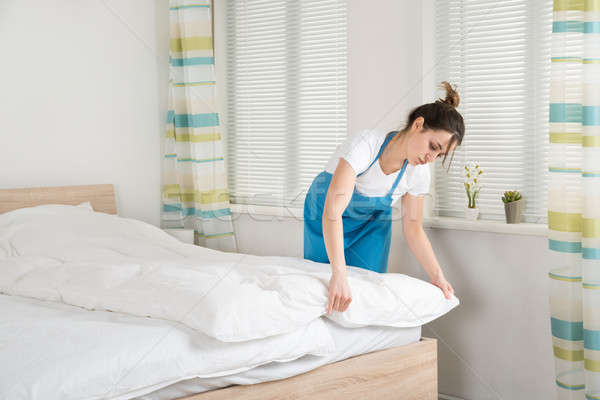 Female Housekeeper Arranging Bedsheet On Bed Stock photo © AndreyPopov
