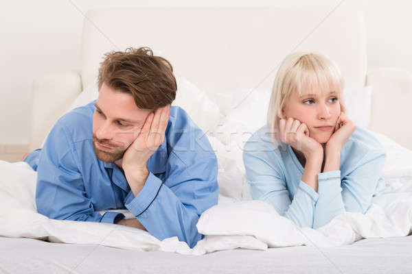 Couple Lying In Bed Ignoring Each Other Stock photo © AndreyPopov