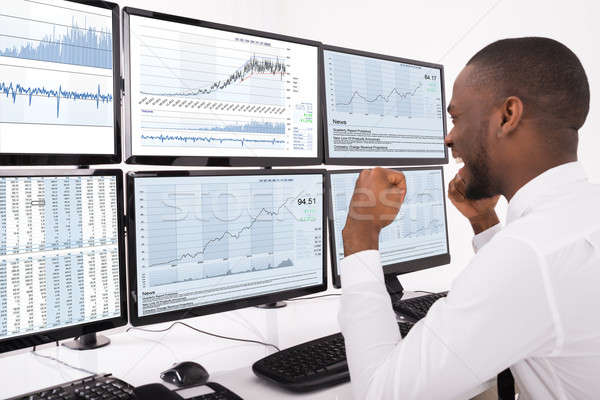Happy Stock Market Broker Looking At Graphs On Multiple Computer Stock photo © AndreyPopov