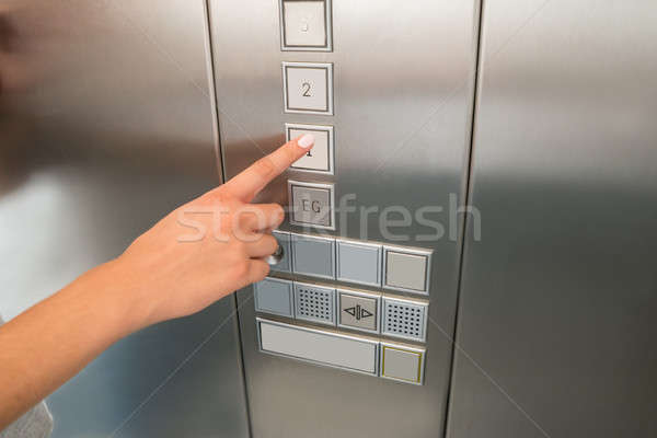 Female's Hand Pressing First Floor Button In Elevator Stock photo © AndreyPopov