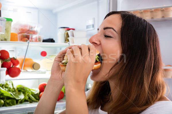 Woman Eating Hamburger Near Fridge Stock photo © AndreyPopov