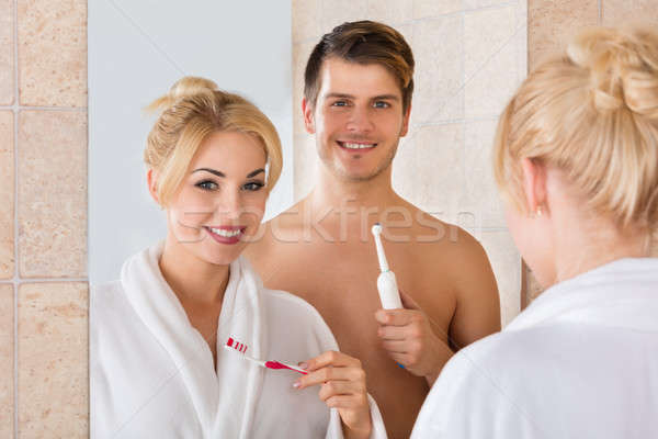 Stock photo: Smiling Couple With Brushing Teeth In Bathroom