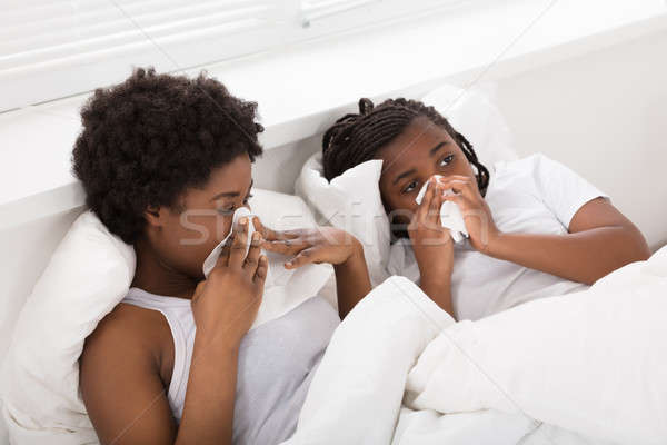 Mother And Daughter Sneezing In Tissues Stock photo © AndreyPopov