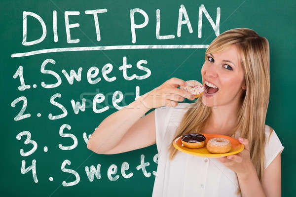 Young Woman Eating Donuts Stock photo © AndreyPopov