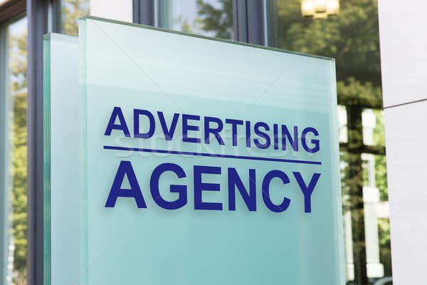 Advertising agency sign on glass board outside building in city Stock photo © AndreyPopov