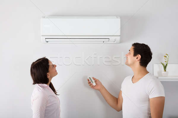 Couple Adjusting Temperature Of Air Conditioner Stock photo © AndreyPopov