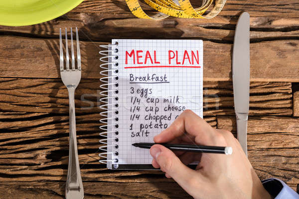 Elevated View Of Human Hand Making Meal Plan On Notebook Stock photo © AndreyPopov