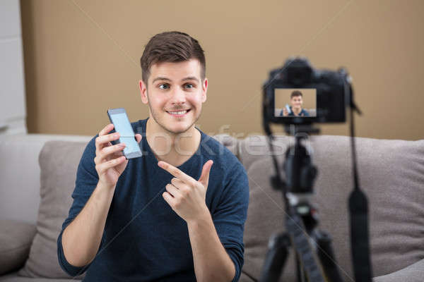 Blogger Holding Mobile Phone Recording Video With Camera Stock photo © AndreyPopov