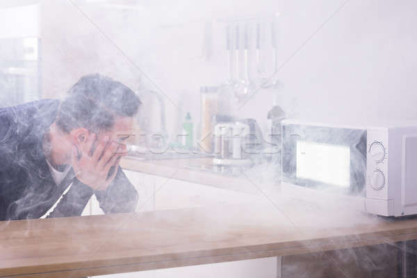 Man Looking At Fire Coming From Microwave Oven Stock photo © AndreyPopov