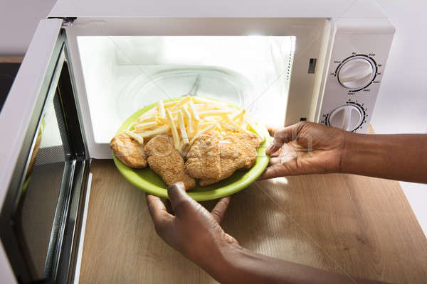 Person Heating Fried Food In Microwave Oven Stock photo © AndreyPopov