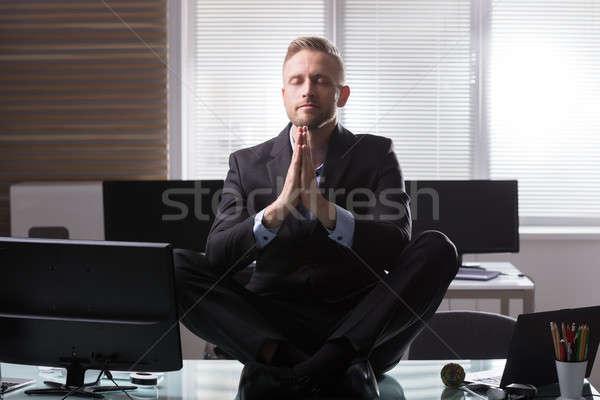 Businessman Meditating In Office Stock photo © AndreyPopov