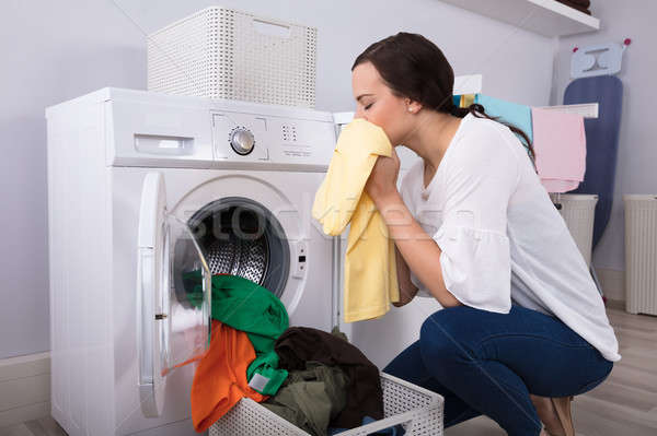 Woman Smelling Cleaned Yellow Cloth Near Washing Machine Stock photo © AndreyPopov