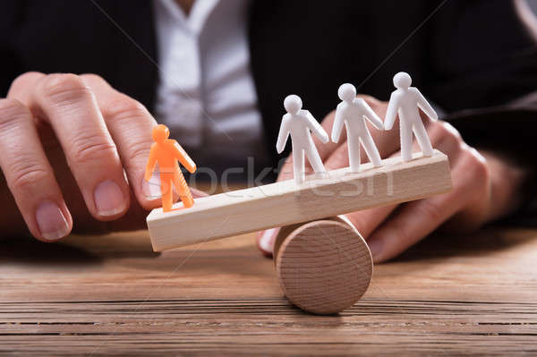 Close-up Of Orange Figure Against White Human Figures On Seesaw Stock photo © AndreyPopov