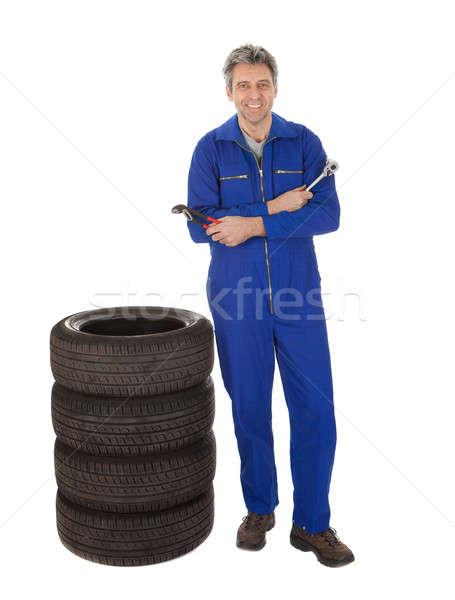 Automechanic standing next to car tires Stock photo © AndreyPopov