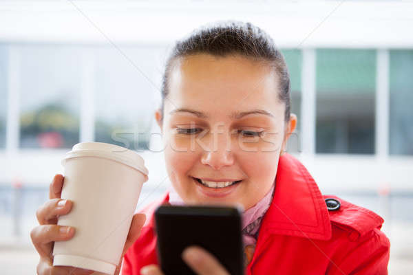 Young woman holding disposable cup and using cell phone Stock photo © AndreyPopov