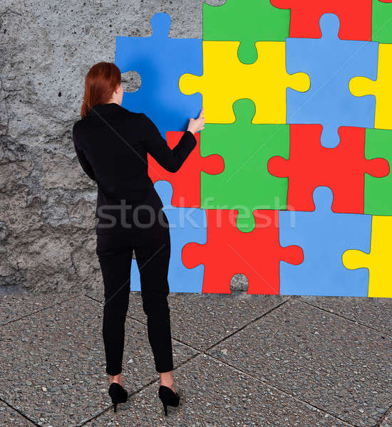 Businesswoman Solving Colorful Jigsaw Puzzle Stock photo © AndreyPopov