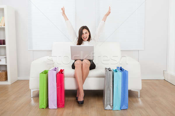 Stock photo: Excited Businesswoman With Laptop Shopping Online On Sofa