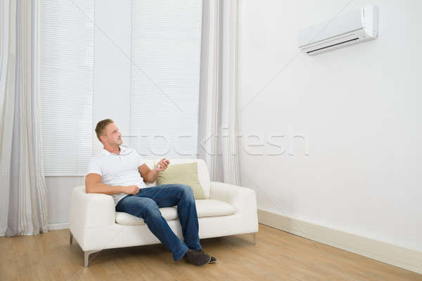 Man Adjusting The Temperature Of Air Conditioner Stock photo © AndreyPopov