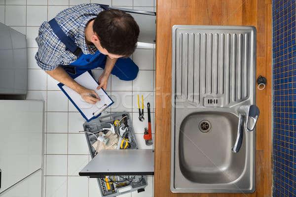 Plumber Examining Kitchen Sink Stock photo © AndreyPopov