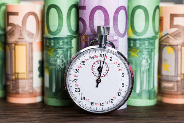 Stopwatch In Front Of Banknotes Stock photo © AndreyPopov