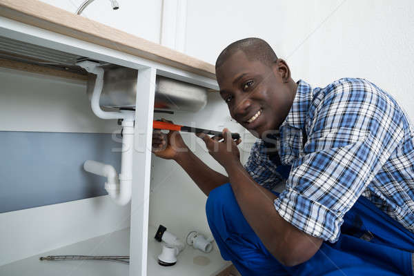 Male Plumber Fixing Pipe Of Sink stock photo © Andriy Popov ...