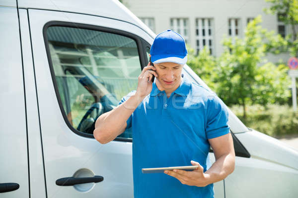 Worker With Mobile Phone And Digital Tablet Stock photo © AndreyPopov