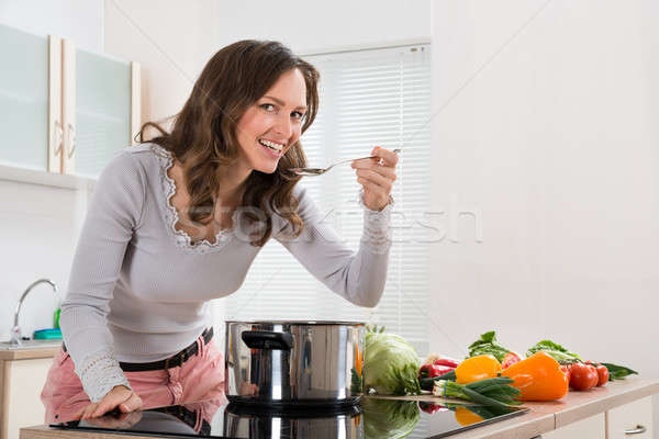 Woman Smiling While Tasting Meal In Kitchen Stock photo © AndreyPopov