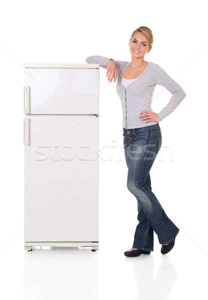 Woman Leaning On Refrigerator Over White Background Stock photo © AndreyPopov