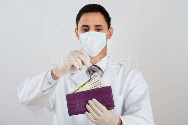 Male Surgeon Removing Banknote From Wallet Stock photo © AndreyPopov