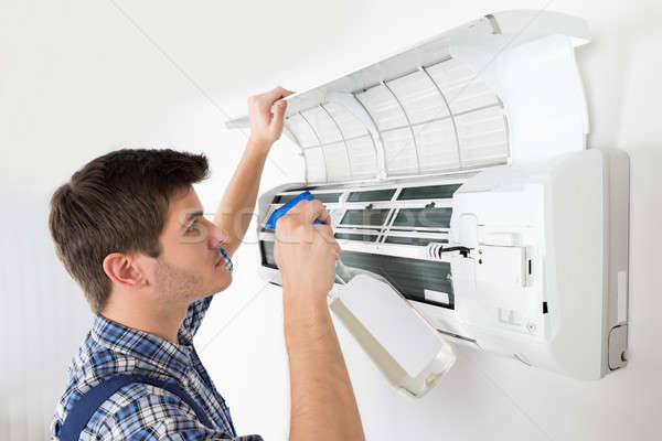 Male Technician Cleaning Air Conditioner Stock photo © AndreyPopov