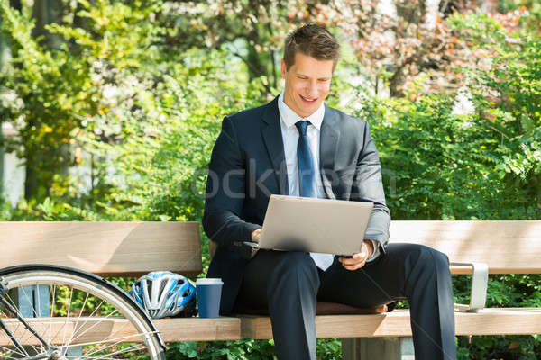 Businessman Sitting On Bench Using Laptop Stock photo © AndreyPopov