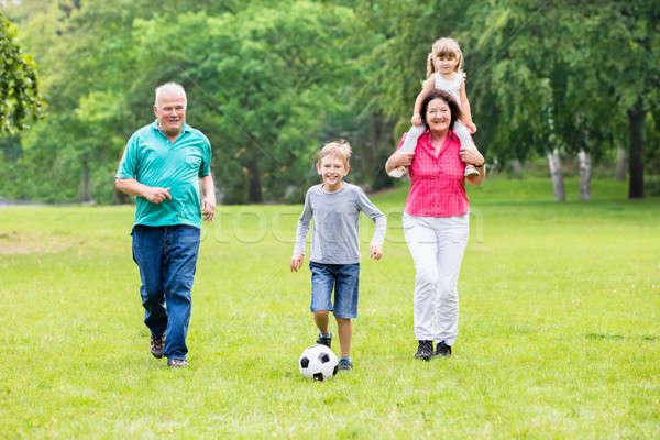 Foto stock: Abuelo · nietos · jugando · balón · de · fútbol · junto · familia · feliz