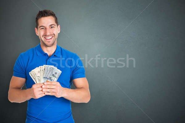 Happy Man Holding Currency Notes Stock photo © AndreyPopov