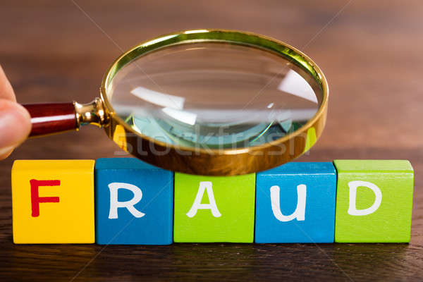 Person Hand With Magnifying Glass And The Word Fraud Stock photo © AndreyPopov
