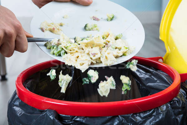 Person Throwing Cooked Pasta In Trash Bin Stock photo © AndreyPopov