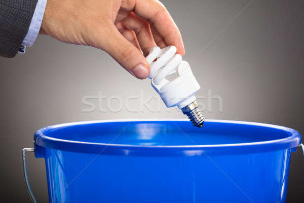 Hand Throwing Energy Efficient Light Bulb In Blue Bucket Stock photo © AndreyPopov