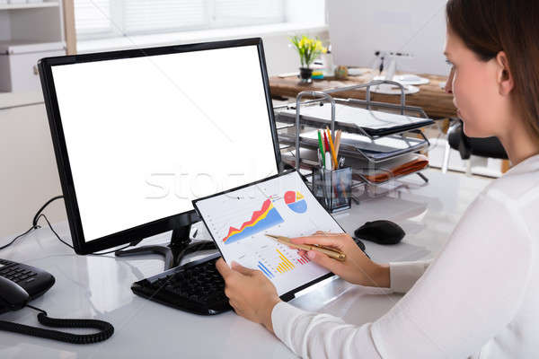 Businesswoman Analyzing Graph In Office Stock photo © AndreyPopov