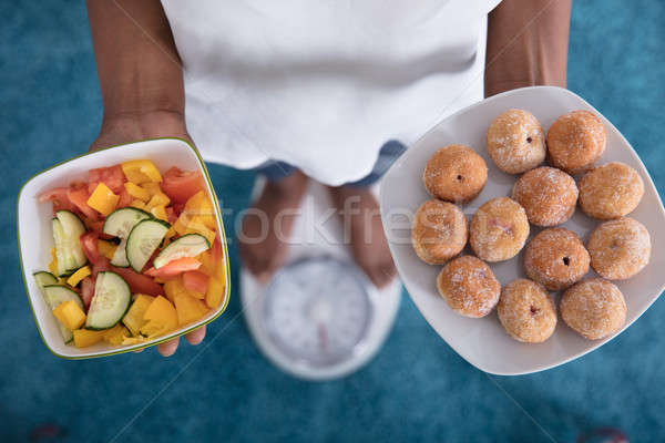Person Standing On Weighing Scale Holding Salad And Cookies Stock photo © AndreyPopov