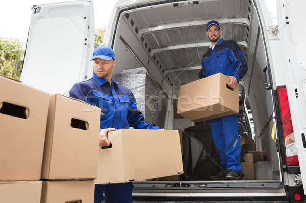 Two Movers Carrying Cardboard Box Stock photo © AndreyPopov