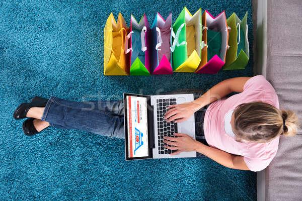 Mulher sessão tapete compras on-line usando laptop Foto stock © AndreyPopov