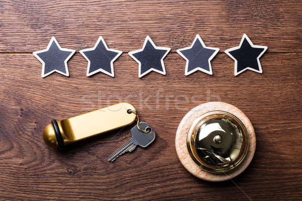 Five Stars, Service Bell And Hotel Key On Wooden Desk Stock photo © AndreyPopov