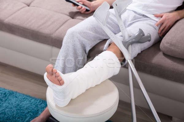 Сток-фото: человека · сломанной · ногой · сидят · диван · молодым · человеком