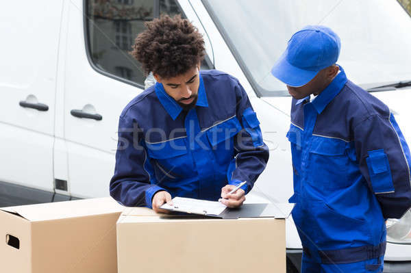 Delivery Man Writing On The Clipboard Stock photo © AndreyPopov