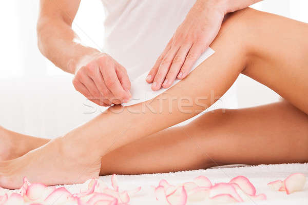 Beautician waxing a woman leg Stock photo © AndreyPopov